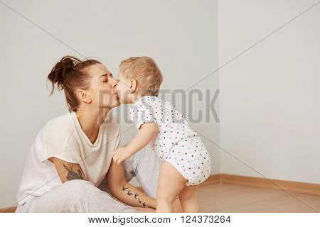 Mother And Child On A White Bed. Mom And Baby Boy In Diaper Playing In Sunny Bedroom. Parent And Lit