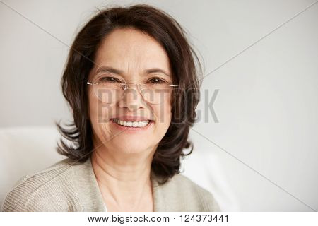 Attractive Middle-aged Brunette Woman With A Beautiful Smile Sitting Against Apartments Background L