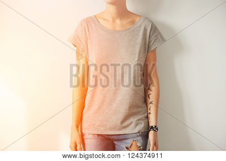 Young tattooed woman wearing grey blank t-shirt.