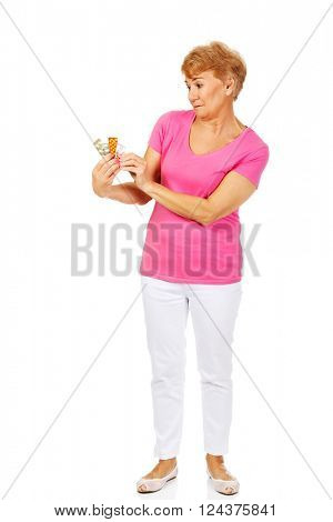 Shocked senior woman holding few tablets package