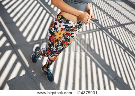 Young Caucasian Woman Wearing Sports Wear Looking At Mobile Phone. Female Athlete Listening Music Wi