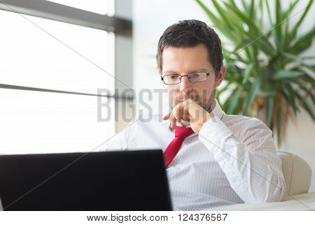 Portrait of successful young businessman in bright modern office focused on work on his laptop computer wearing glasses. Business and entrepreneurship concept.