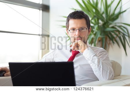 Portrait of successful young businessman wearing glasses in bright modern office with his laptop computer . Business and entrepreneurship concept.