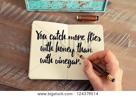 Retro effect and toned image of a woman hand writing on a notebook. Handwritten quote You catch more flies with honey than with vinegar as inspirational concept image