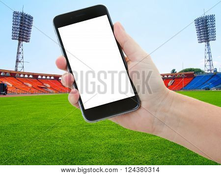 football sport background - football field with green grass and hands holding phone with blank screen