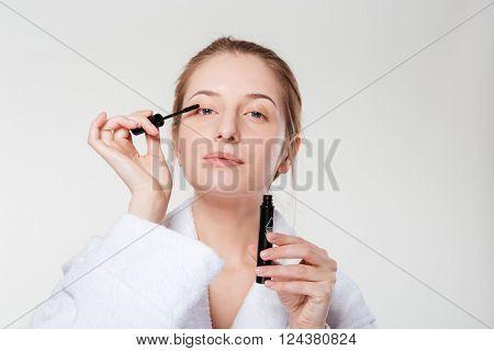 Woman applying mascara on eyelashes isolated on a white background