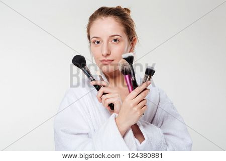 Beautiful woman holding makeup brushes isolated on a white background