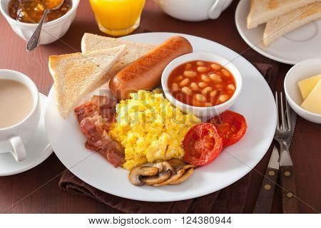 full english breakfast with scrambled eggs, bacon, sausage, beans, tomato