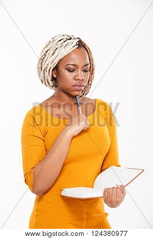 Thoughtful young african american woman in yellow dress thinking and writing in notebook over white background