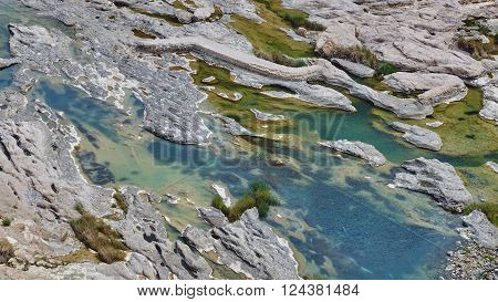 Emerald green pools of water in pockets of eroded rock formations