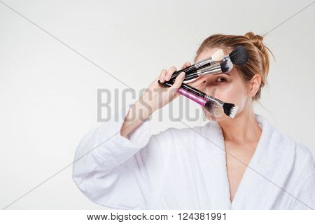 Woman in bathrobe holding makeup brushes isolated on a white background