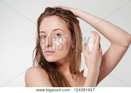 Attractive woman spraying hairspray isolated on a white background
