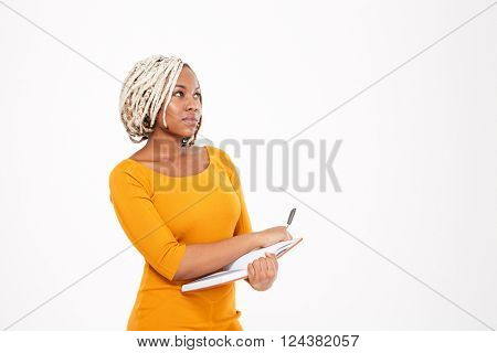Thoughtful pretty young african american woman writing in notebook and thinking over white background