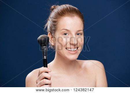 Beauty portrait of a happy woman holding makeup brush over blue background