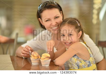 Little cute girl eating ice creams with her mother