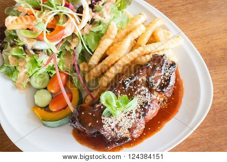 Delicious barbecued ribs with spicy sauce and organic salad stock photo