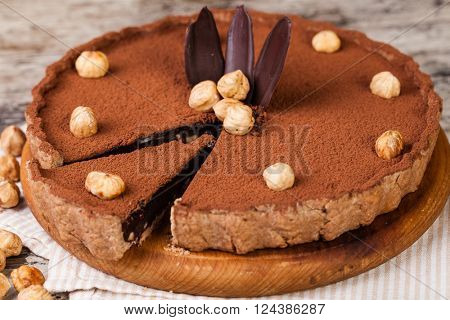 chocolate tart with hazelnuts on a wooden plate