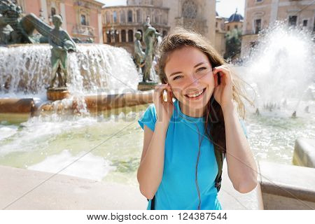Woman listening to music on earphones in Valencia Spain. Travel and tourism concept.