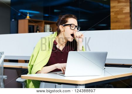 Pretty overworked young businesswoman in glasses yawning and using laptop on workplace