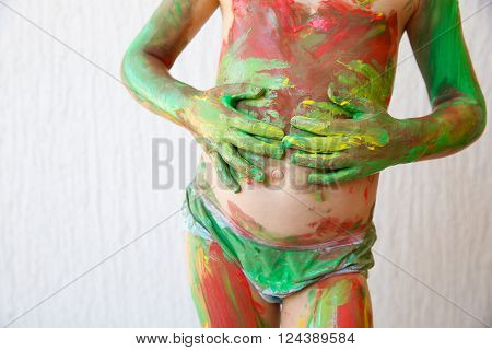 Little girl body painting herself with non-toxic, washable finger paints, having fun with creative playing. Sensory play, innovative approach to learning, wild child concept.