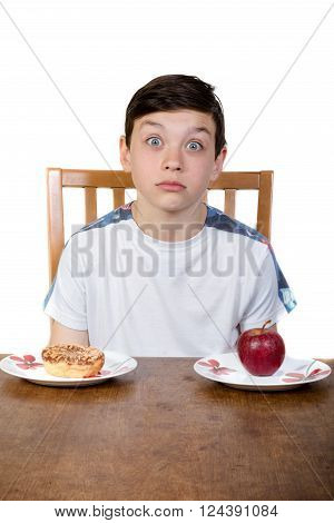 Young boy making up his mind to eat either a donut or an apple.