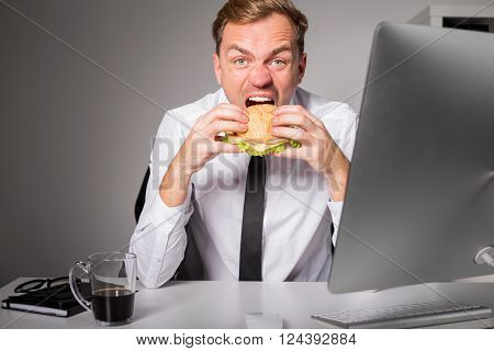 Hungry man at the office eating burger