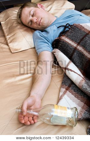 A young man sleeping on the couch with a bottle of wiskey