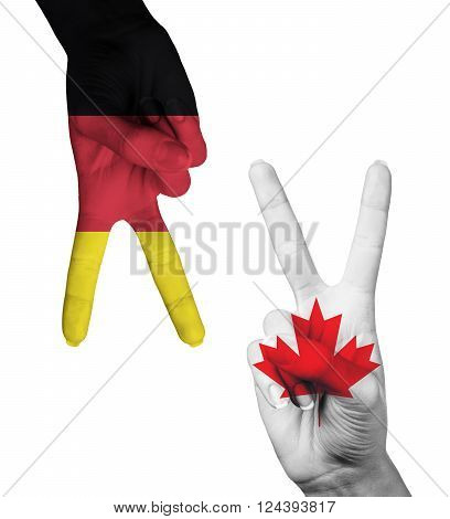 Hands making the V sign as symbol of victory. Germany and Canada flags painted on hands isolated on white background