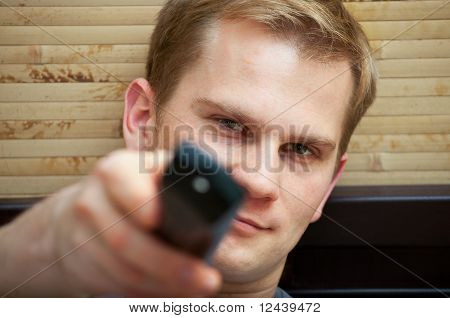 Junger Mann, Blick in die Kamera beim Umschalten von TV-Kanäle