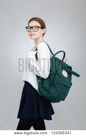 Portrait of beautiful teenage girl in glasses with green backpack standing