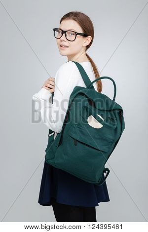 Happy pretty teenage girl in glasses with backpack standing and looking back