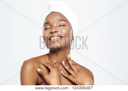 Smiling relaxed afro american woman with towel on head standing isolated on a white background