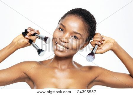 Smiling afro american woman holding makeup brushes isolated on a white background