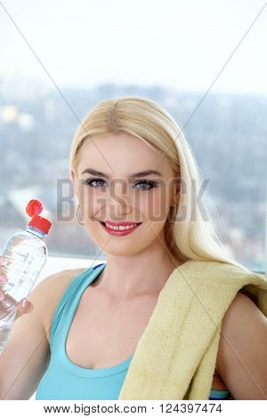Sportswoman drinks water from a plastic bottle. Concept: sports, fitness at home, shaping, aerobics, healthy lifestyle.