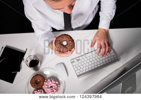 Man at the office working on computer and  eating donuts