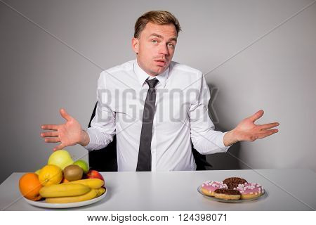 Man choosing between healthy and unhealthy food