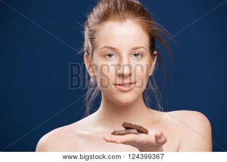 Young woman holding chocolate over blue background