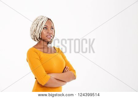 Portrait of attractive pensive young african american woman standing with arms crossed and looking up over white background