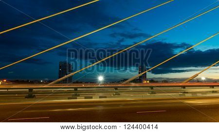 The bridge construction on twilight and river reflection at night Rama 8 Bridge in Bangkok Thailand