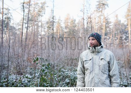 Young man standing outdoors wearing warm clothing and a beanie, with a winter forest behind him and greenery covered in a layer of white frost