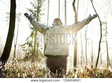 Man standing in a forest wearing warm clothing on a cold winter day, closing his eyes and  lifting his arms up in celebration of nature, with sunflare shining through the trees