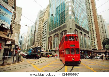 HONG KONG, CHINA - FEB 12: Motion of red double-decker tram on street with huse modern buildings on February 12, 2016. Hong Kong dollar is the eighth most traded currency in the world.
