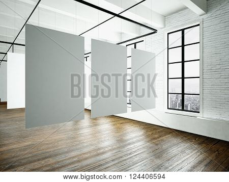 Museum expo interior in modern building.Open space studio.Empty white canvas hanging.Wood floor, bricks wall, panoramic windows.Blank frames ready for bussiness information.Horizontal.