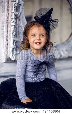 portrait of a little girl 2 years in the Studio in a black mask and a big bow