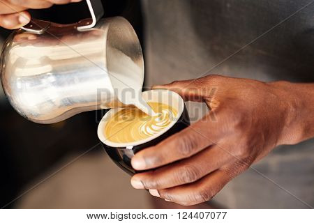 Hands of a skilled African barista pouring frothy milk from a stainless steel jug into a ceramic coffee cup, and forming an attractive pattern on top of the cappucino he is busy making