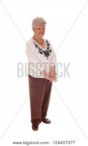 A senior citizen woman standing full length in brown pants and sweater