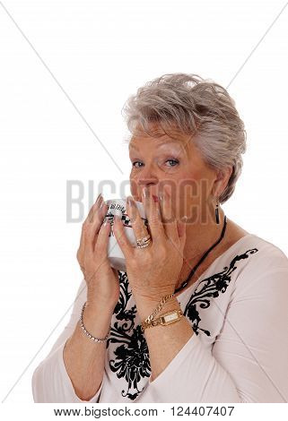 A beautiful senior woman holding a bowl in her hands and drinking