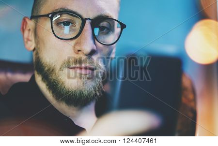Photo bearded businessman relaxing modern loft office. Banker sitting in vintage chair, looking mobile phone. Using contemporary smartphone. Blurred background. Horizontal