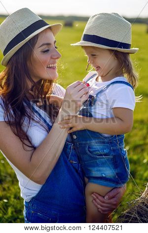 daughter with mom standing in the field at the sheaf in hats and denim jumpsuits during sunset