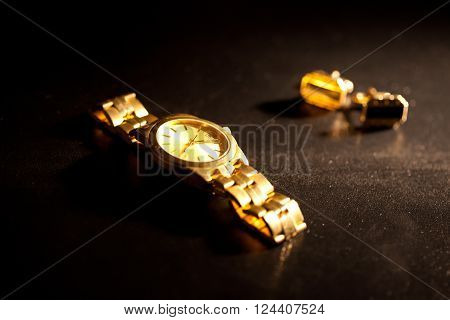 Gold watches and cufflinks on a black background.